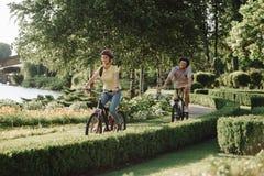 循环在公园的年轻快乐的夫妇 库存照片