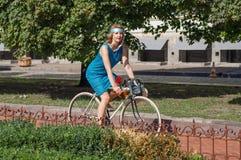 循环在城市公园的减速火箭的衣物的活跃少妇 免版税库存照片