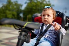 循环在城市公园的自行车位子的逗人喜爱的愉快的矮小的婴孩 免版税图库摄影