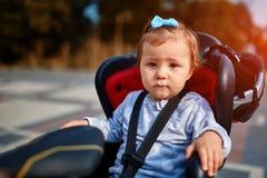 循环在城市公园的自行车位子的逗人喜爱的愉快的矮小的婴孩 免版税库存图片