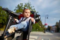 循环在城市公园的自行车位子的逗人喜爱的愉快的矮小的婴孩 库存照片