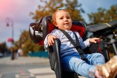 循环在城市公园的自行车位子的逗人喜爱的愉快的矮小的婴孩 免版税库存照片