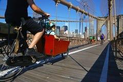 循环在布鲁克林大桥,纽约的人们 库存图片