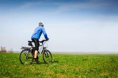 循环在春天公园的年轻骑自行车者 免版税库存照片