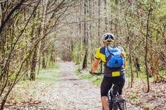 循环在春天公园的年轻骑自行车者 免版税图库摄影