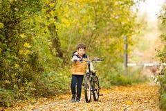 循环在晴朗的秋天公园的逗人喜爱的小男孩 免版税库存照片