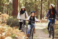 循环在有他们的女儿的一个森林里的女同性恋的夫妇 免版税库存照片