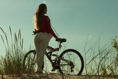 循环在沙子的无法认出的妇女自行车 库存照片