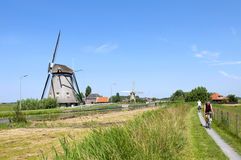 循环在沿古老风车的狭窄的自行车道路 免版税库存图片