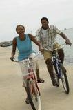 循环在海滩的夫妇 库存图片