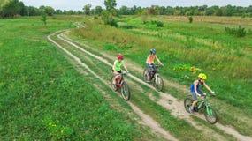 循环在自行车户外鸟瞰图的家庭从上面,有孩子的愉快的活跃母亲获得乐趣,家庭体育 免版税图库摄影