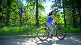 循环在自行车的骑自行车的妇女 运动的妇女骑马自行车在夏日 女性骑自行车者室外活动居住健康 影视素材