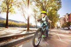 循环在自行车道路的愉快的男孩在秋天城市 免版税库存图片