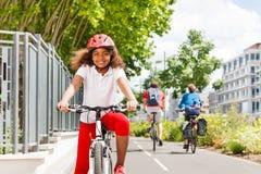 循环在自行车道路的愉快的非洲女孩在城市 免版税图库摄影