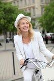 循环在镇里的快乐的中年妇女 免版税库存图片