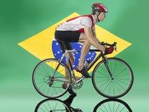 循环在巴西旗子前面的男性骑自行车者 免版税图库摄影
