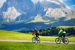 循环在Seiser Alm,最大的高处高山草甸的游人在欧洲,在背景的惊人落矶山脉 库存照片