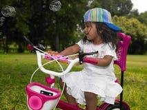 循环女孩她的公园骑马 免版税库存照片