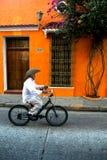 循环沿静街过去五颜六色的橙色房子的牛仔帽的老人 图库摄影
