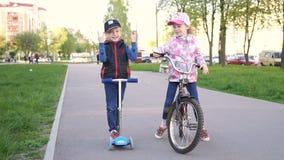 循环的小女孩,小男孩在公园乘坐一辆滑行车 股票录像