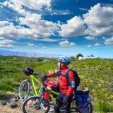 循环的旅游骑自行车者在有paniers的佩德拉尔瓦巴伦西亚 免版税库存照片