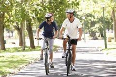 循环通过公园的成熟夫妇 库存图片