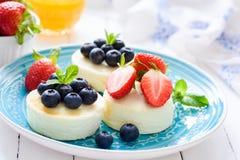 微型乳酪蛋糕或syrniki或者酸奶干酪薄煎饼用新鲜的莓果在蓝色板材 免版税库存图片