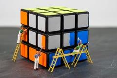 微型人工作者绘画立方体 免版税库存照片