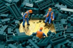 微型人建筑工人在一个绿色水罐块中间开掘金位硬币 投资的通信在Digi 免版税图库摄影