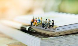 微型人民坐书使用当背景教育或企业概念 免版税图库摄影