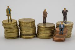微型人民坐堆硬币 免版税图库摄影