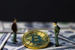微型人民小形象站立的商人和谈论在金黄bitcoin之间的事务在一百美元钞票 免版税库存图片