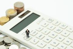 微型人民支付年税时间手表的年收入税在木词税和白色键盘投入利用的队列 免版税库存图片