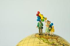 微型人民计算拿着气球的愉快的家庭站立o 免版税图库摄影