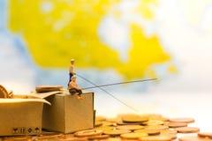 微型人民,人们使用钓鱼竿采取从地板和下落堆硬币的金钱在箱子 使用作为乱砍strate 库存照片