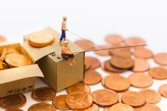 微型人民,人们使用钓鱼竿采取从地板和下落堆硬币的金钱在箱子 免版税库存照片