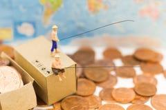 微型人民,人们使用钓鱼竿采取从地板和下落堆硬币的金钱在箱子 免版税图库摄影