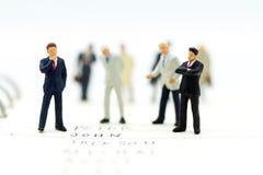 微型人民,小组商人与队一起使用,使用当适合的雇员的背景选择, 免版税库存照片