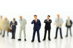 微型人民,小组商人与队一起使用,使用当适合的雇员的背景选择, 库存照片