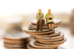 微型人民,老夫妇计算坐在堆硬币顶部 图库摄影