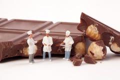 微型人民:一位厨师和厨师在巧克力块前面 库存照片