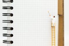 微型人民:与梯子的微型图和在书前面的白色油漆 免版税库存图片
