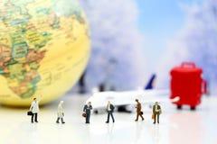 微型人民:与飞机, worldmap,行李的商人  免版税图库摄影