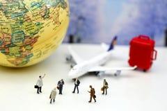 微型人民:与飞机, worldmap,行李的商人  免版税库存图片