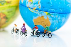 微型人民:人小组有世界地图的骑马自行车 r 免版税库存图片