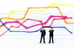 微型人民:商人仪表板,显示图表,背景利润率立场前面  浓缩的事务的图象用途 免版税库存照片