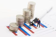 微型人民:商人在图表赚从工作的钱,堆硬币被安置 用途作为企业概念 库存图片