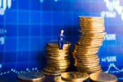 微型人民:商人坐与图表的硬币在墙壁上 企业竞争概念的图象用途 免版税图库摄影