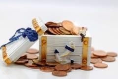 微型人民:商人坐与硬币的块 Busin 免版税库存照片