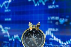 微型人民:商人坐指南针仪表板,显示图表,背景利润率指南前面  库存图片